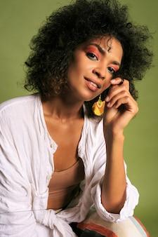 Sluit omhoog portret van afrikaanse vrouw met heldere kleurrijk; make-up poseren.