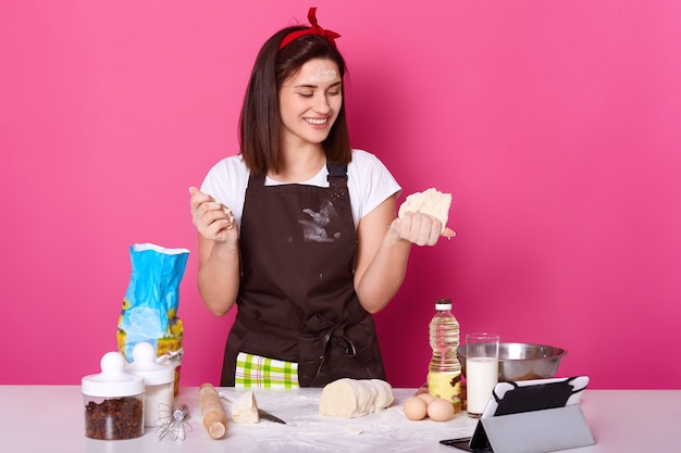 Sluit omhoog portret van bakker die in schort pastei gevulde bakkerij voorbereiden, huisvrouw voorbereidend op pasen