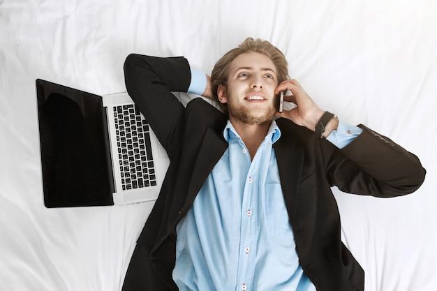 Sluit omhoog portret van blije knappe zakenman liggend op bed in kostuum met laptop en celtelefoon. praten met de klant, blij zijn met zijn werk.