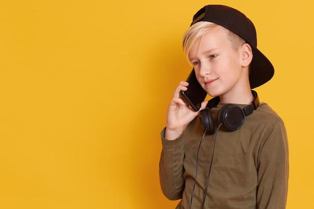 Sluit omhoog portret van blondejongen die door mobiele telefoon spreken en prettige gelaatsuitdrukking hebben, het charmante model stellen geïsoleerd op geel. kopieer ruimte voor reclame of promotie.