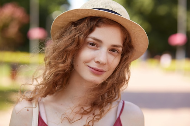 Sluit omhoog portret van charmant krullend haired aanbiddelijk meisje die natuurlijke blik hebben, gelukkig zijn om bij lokaal groen park te rusten, in goede stemming zijn, direct bekijkend camera. mensen en emoties concept.