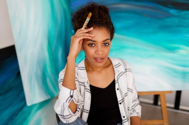 Sluit omhoog portret van charmante vrouw met het donkere huid stellen in haar kunststudio met abstracte schilderijen.