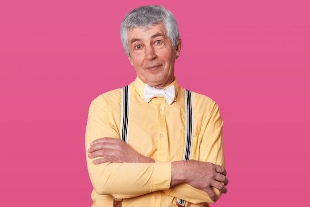Sluit omhoog portret van de bejaarde mens met geel overhemd en witte vlinderdas, direct bekijkend camera, houdt handen gevouwen, vrije spase voor uw reclame of bevordering, geïsoleerd op roze studio.