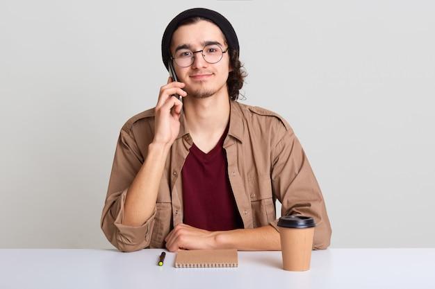 Sluit omhoog portret van de drukke creatieve mens roept zakenpartner om toekomstige vergadering te bespreken, heeft nieuw idee, freelancer die iets in zijn notitieboekje schrijft en koffie drinkt, die over witte studiomuur wordt geïsoleerd