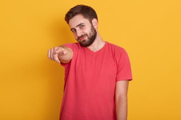 Sluit omhoog portret van de gelukkige jonge camera richten en mens die terwijl, dragend rode toevallige t-shirt glimlachen
