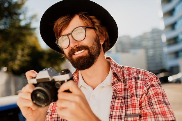 Sluit omhoog portret van de glimlachende hipster-baardmens gebruikend retro filmcamera