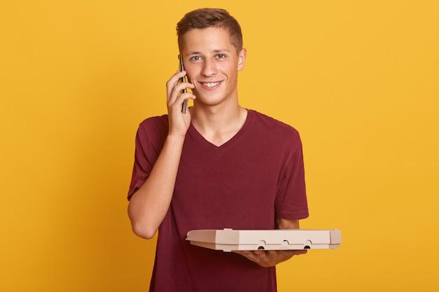 Sluit omhoog portret van de jonge de pizzadozen van de leveringsmens in handen hebben en gesprek via mobiele telefoon hebben, terloops dragend, bekijkend glimlachend camera, stellen geïsoleerd op geel.