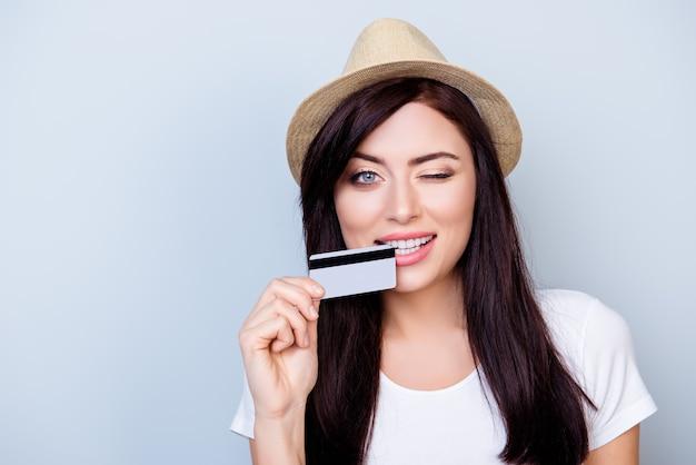 Sluit omhoog portret van de jonge gelukkige creditcard van de vrouwenholding tegen grijze ruimte