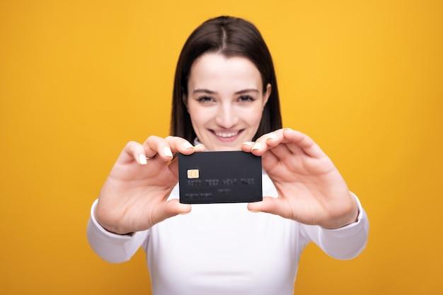 Sluit omhoog portret van de jonge glimlachende creditcard van de bedrijfsvrouwenholding, die op gele achtergrond wordt geïsoleerd.