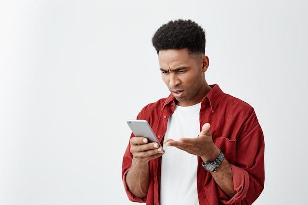Sluit omhoog portret van de jonge knappe tan-gevilde mens met afrokapsel in toevallig wit t-shirt met rood overhemd bekijkend telefoon met verwarde uitdrukking, ruzie met vriendin.