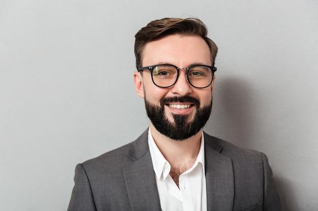 Sluit omhoog portret van de kaukasische ongeschoren mens die in oogglazen op camera met oprechte glimlach kijken, die over grijs wordt geïsoleerd
