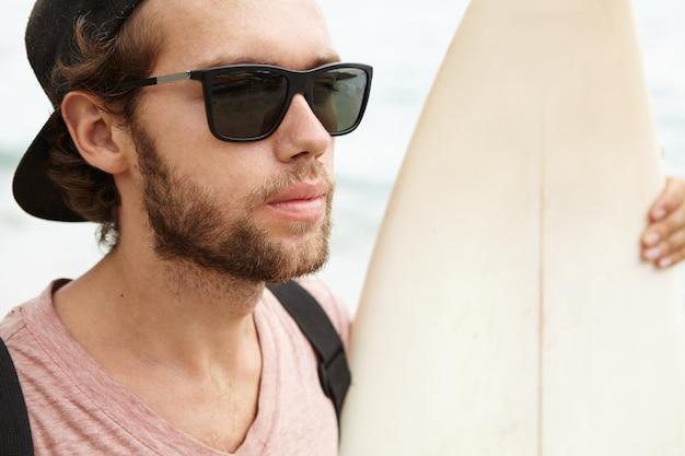 Sluit omhoog portret van de knappe jonge mens met verwarde baard die zonnebril dragen en honkbal glb achteruit zijn witte surfplank houden en oceaan bekijken