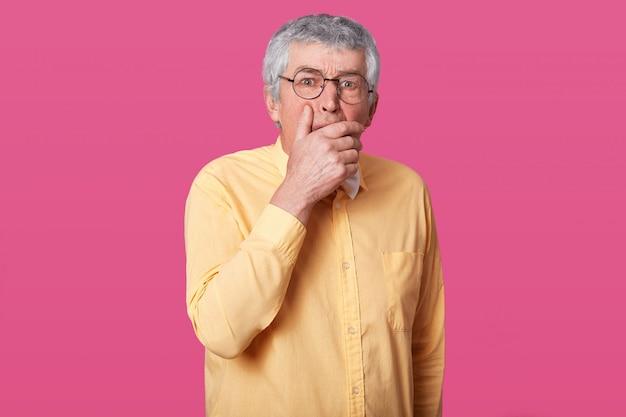Sluit omhoog portret van de mens met zwarte ronde glazen, gekleed geel overhemd en vlinderdas. bejaarde senior met wijd open ogen, heeft geschokte gezichtsuitdrukking, ergens bang voor, met mond met hand.