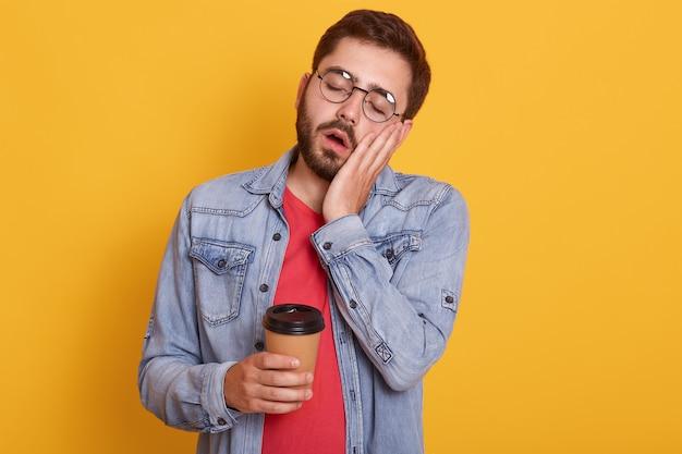 Sluit omhoog portret van de mens over geïsoleerde geel, nemend koffie in meeneemdocument kop, stellend met gesloten ogen en open mond, houdt hand op wang, dragend rood overhemd en spijkerjasje.