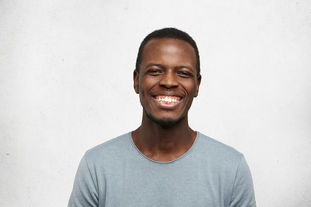 Sluit omhoog portret van de vrolijke jonge zwarte mens die in grijze t-shirt breed glimlachen