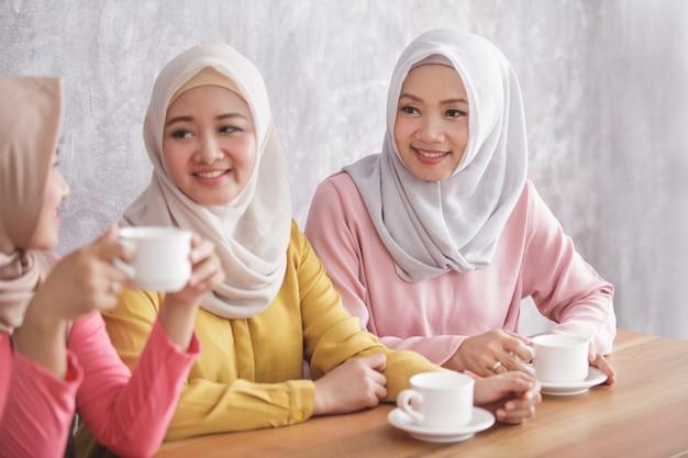Sluit omhoog portret van drie mooie broers en zussen die samen een koffietijd hebben