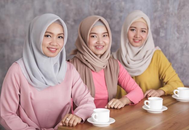Sluit omhoog portret van drie mooie moslimvrouw die samen een koffietijd hebben