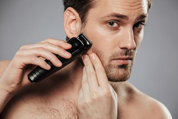 Sluit omhoog portret van een ernstige shirtless mens het scheren baard