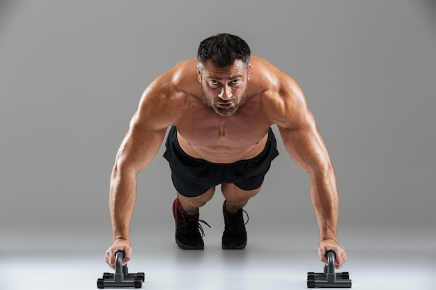 Sluit omhoog portret van een ernstige sterke shirtless mannelijke bodybuilder
