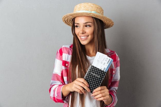 Sluit omhoog portret van een glimlachende gelukkige vrouwenreiziger in het paspoort van de strohoedholding met vliegtuigkaartjes