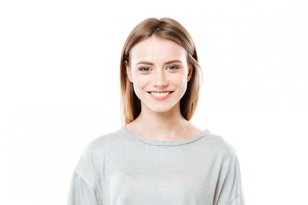 Sluit omhoog portret van een glimlachende jonge vrouw die camera bekijkt