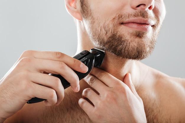 Sluit omhoog portret van een glimlachende mens die zijn baard scheert