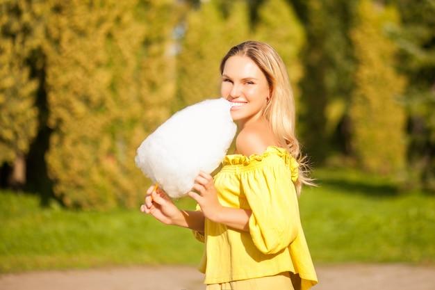 Sluit omhoog portret van een glimlachende opgewekte gesponnen suiker van de meisjesholding bij park