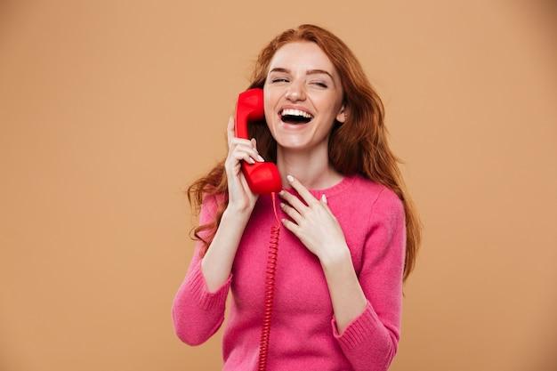 Sluit omhoog portret van een jong mooi roodharigemeisje die door klassieke rode telefoon spreken