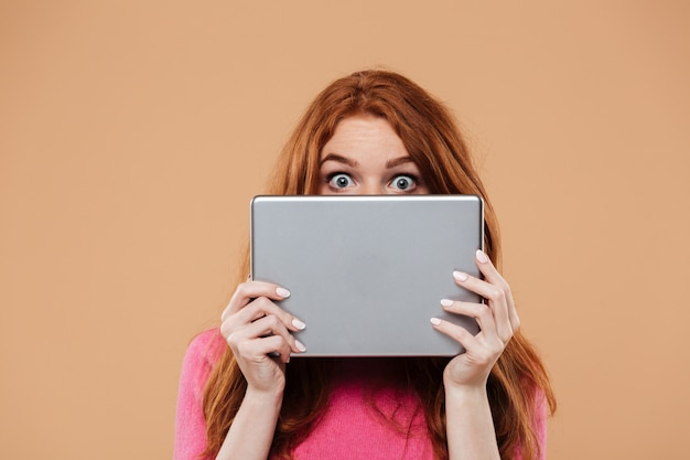 Sluit omhoog portret van een jong roodharigemeisje die gezicht behandelen met digitale tablet