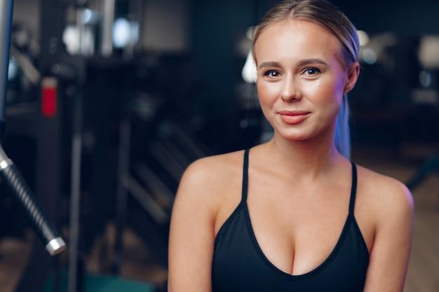 Sluit omhoog portret van een jonge blondevrouw in sportbustehouder in een donkere gymnastiek