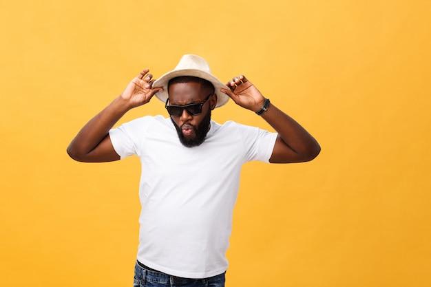 Sluit omhoog portret van een jonge mens die met handen lachen die hoed houden isoleren over gele achtergrond