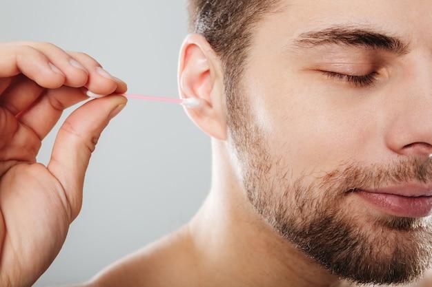 Sluit omhoog portret van een jonge mens die zijn oren schoonmaakt