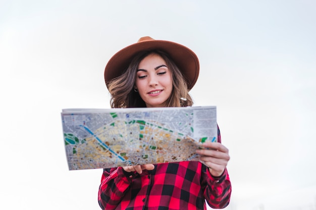 Sluit omhoog portret van een jonge mooie vrouw die vrijetijdskleding draagt, kijkend een kaart