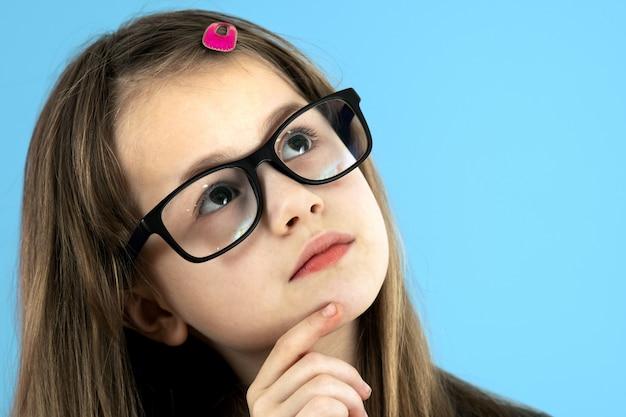 Sluit omhoog portret van een kindschoolmeisje die kijkend glazen dragen die hand houden aan haar gezicht denkend over iets geïsoleerd op blauwe achtergrond.