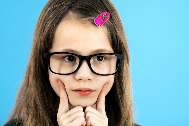 Sluit omhoog portret van een kindschoolmeisje die kijkend glazen dragen die hand houden aan haar gezicht denkend over iets geïsoleerd op blauwe muur
