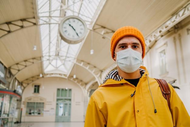 Sluit omhoog portret van een mens in beschermend medisch masker, oranje gebreide glb en geel jasje bij leeg station, denkend hoe het coronavirus te vermijden. covid-19 virusconcept.