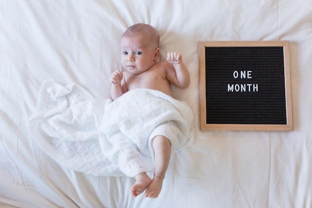Sluit omhoog portret van een mooie baby op witte achtergrond thuis met een uitstekend brievenbord met bericht: één maand