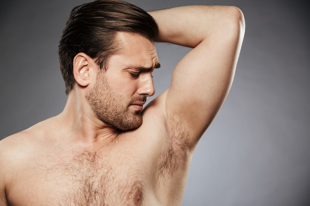 Sluit omhoog portret van een shirtless mens die zijn oksel ruikt