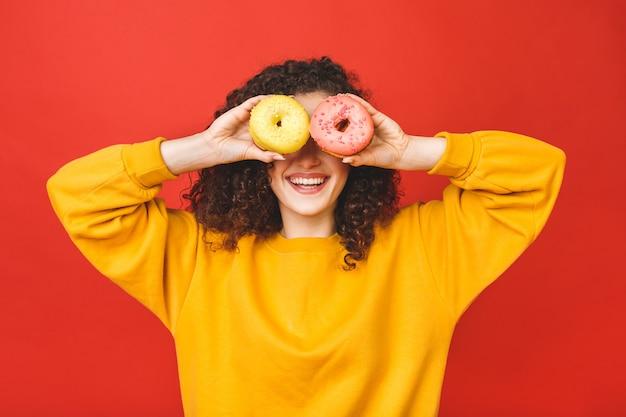 Sluit omhoog portret van een tevreden vrij jong meisje dat donuts eet dat over rode achtergrond wordt geïsoleerd.