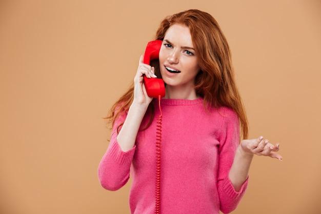 Sluit omhoog portret van een verward mooi roodharigemeisje die door klassieke rode telefoon spreken