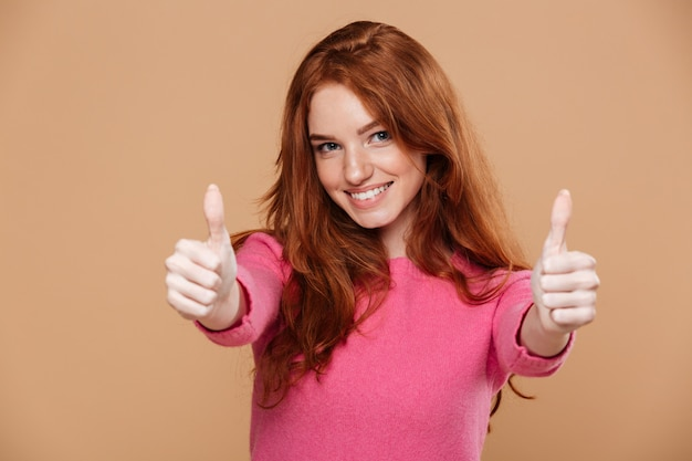 Sluit omhoog portret van een vrolijk mooi roodharigemeisje met omhoog duimen