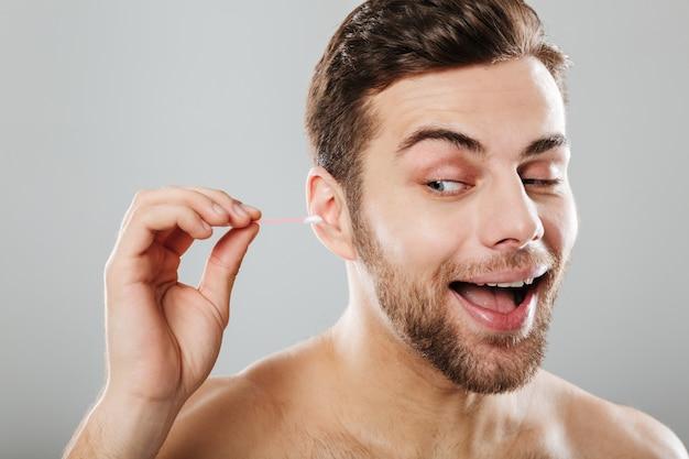 Sluit omhoog portret van een vrolijke mens die zijn oren schoonmaakt