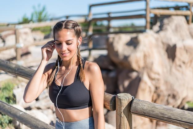 Sluit omhoog portret van een vrouw die sport doen die openlucht het glimlachen en het luisteren muziek rusten
