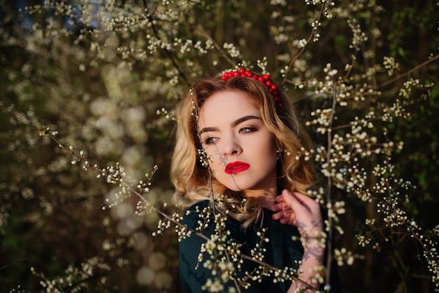 Sluit omhoog portret van elegant blondemeisje van yong bij groene kleding op de tuin in de lente op bloesembomen.