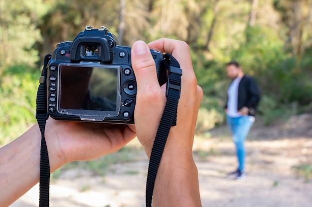 Sluit omhoog portret van fotograafmens die beeld met digitale camera nemen. werk, sessieconcept.