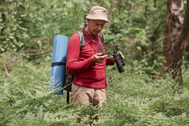 Sluit omhoog portret van geconcentreerd bejaard mannetje die rode toevallige sweater, broek en glb dragen, die zich in bos met kompas bevinden