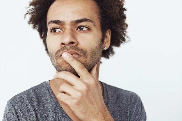 Sluit omhoog portret van geconcentreerd ernstig afrikaans mannetje die over afgelopen en toekomstige plannen denken of dromen waar te gaan eten over witte achtergrond.