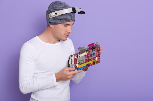 Sluit omhoog portret van geconcentreerde elektronikaingenieur met vergrootglas op zijn hoofd