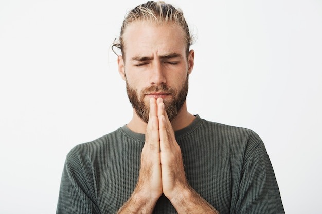 Sluit omhoog portret van geconcentreerde rijpe kerel met modieus kapsel en baardholdingshanden samen voor gezicht, biddend en hoopend