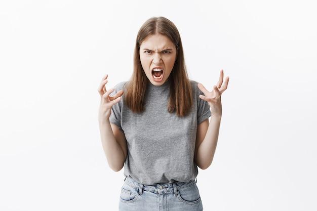 Sluit omhoog portret van gek mooi kaukasisch studentenmeisje met bruin haar in vrijetijdskleding met boze gezichtsuitdrukkingen, gesticulated met handen, die pissig zijn